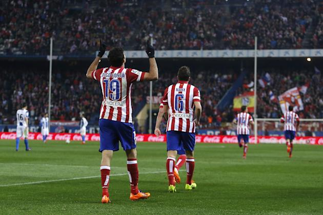 Atletico's Diego Costa, left, celebrates his goal with teammates during a Spanish La Liga soccer match between Atletico Madrid and Espanyol at the Vicente Calderon stadium in Madrid, Spain, Saturd