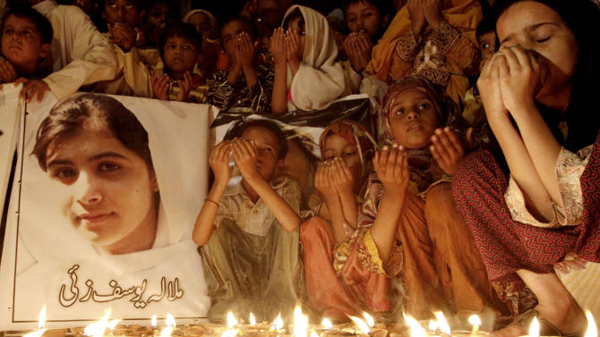 """Pakistani children pray for the recovery of 14-year-old schoolgirl Malala Yousufzai, who was shot on Tuesday by the Taliban for speaking out in support of education for women, during a candlelight vigil in Karachi, Pakistan, Friday, Oct. 12, 2012. A Pakistani military spokesman says Yousufzai is in """"satisfactory"""" condition but cautions that the next few days will be critical. Writing reads on the poster left, """"Malala Yousufzai.""""(AP Photo/Shakil Adil)"""