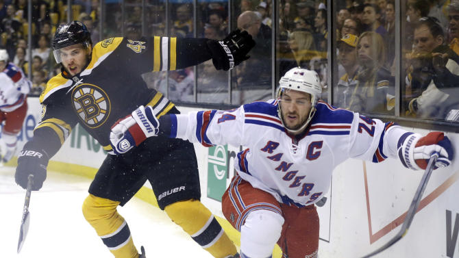 Boston Bruins defenseman Matt Bartkowski (43) and New York Rangers right wing Ryan Callahan (24) grapple along the boards during the first period in Game 2 of the NHL Eastern Conference semifinal hockey playoff series in Boston, Sunday, May 19, 2013. (AP Photo/Elise Amendola)