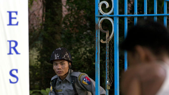 In this picture taken on Saturday, Nov. 17, 2012, a worker carries buckets of paint as a police officer watches outside a gate of Yangon University, where President Barack Obama is scheduled to deliver a speech on Monday, Nov. 19, 2012, in Yangon, Myanmar.  Since colonial times, the fight for change in Myanmar has begun on this leafy campus. It was a center of the struggle for independence against Britain and served as a launching point for pro-democracy protests in 1962, 1974, 1988 and 1996. For many, the school has today become a symbol of the country's ruined education system and a monument to a half century of misrule. (AP Photo/Gemunu Amarasinghe)