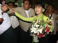 Myanmar democracy leader Aung San Suu Kyi holds a bouquet of flowers as she walks through the international airport in Yangon on September 16. Suu Kyi on Monday opened a sweeping and once-unimaginable tour of the United States, where she will enjoy a hero&#39;s welcome from Americans inspired by her story