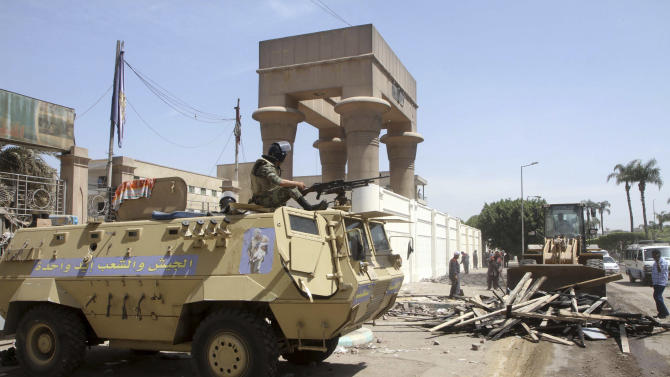 An Egyptian Army soldier sits atop an armored vehicle as workers clear away plywood and debris used by protesters during clashes outside the Ministry of Defense in Cairo, Egypt, Saturday, May 5, 2012.  Lawyers say authorities have detained over 300 Egyptian protesters including 18 women following clashes outside the country's Defense Ministry, accused of attacking troops and disrupting public order.(AP Photo/Mahmoud Abd Al-Aziz)