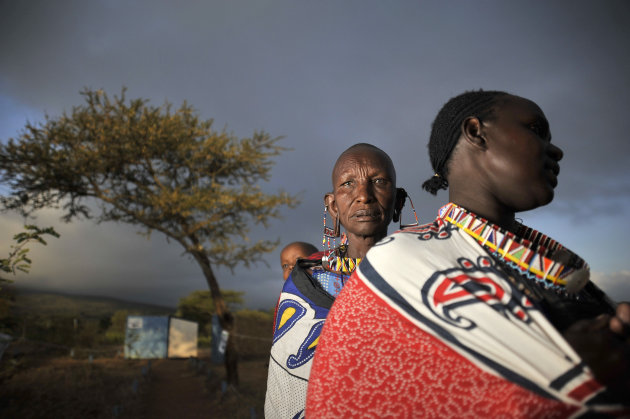 Masaai women line up at dawn to vote in a general election in Kumpa, Kenya, Monday, March 4, 2013. Five years after more than 1,000 people were killed in election-related violence, Kenyans went to the polls on Monday to begin casting votes in a nationwide election seen as the country's most important - and complicated - in its 50-year history. (AP Photo/Riccardo Gangale)