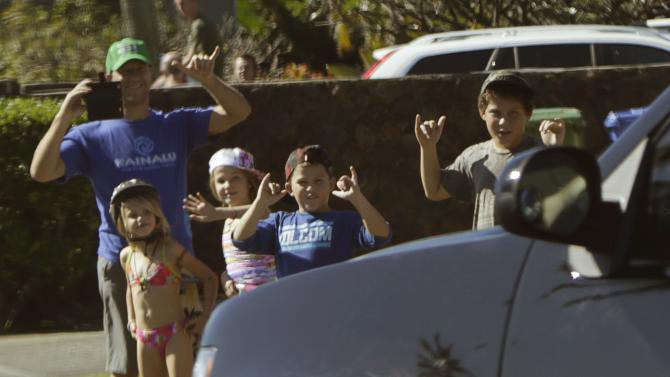 US President Obamas motorcade passes by local family on Christmas Day in Kailua during Hawaiian holiday vacation