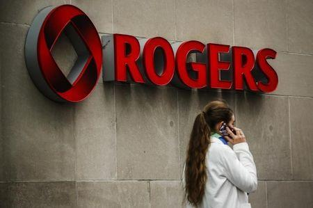 A woman speaks on her phone in front of a Rogers Communications Inc sign before the company's AGM in Toronto