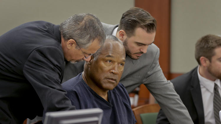 O.J. Simpson, center, talks with defense attorneys Ozzie Fumo, left, and Josh Barry during an evidentiary hearing in Clark County District Court, Thursday, May 16, 2013 in Las Vegas. Simpson, who is currently serving a nine to 33-year sentence in state prison as a result of his October 2008 conviction for armed robbery and kidnapping charges, is using a writ of habeas corpus, to seek a new trial, claiming he had such bad representation that his conviction should be reversed. (AP Photo/Julie Jacobson, Pool)
