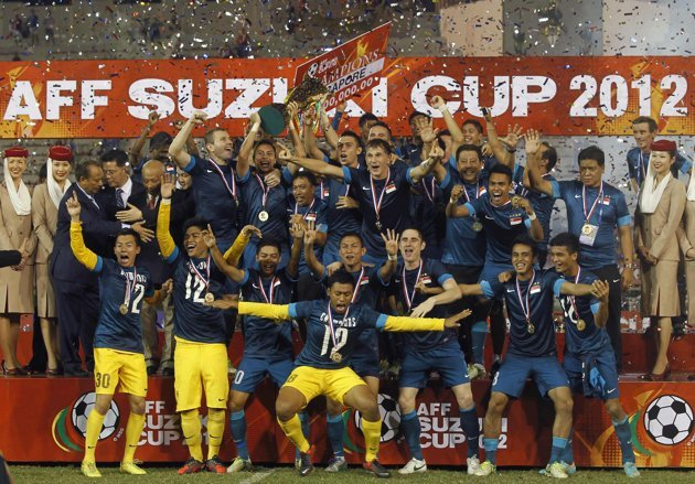 Singapore's team players and staff celebrate with the trophy after their AFF Suzuki Cup 2012 win over Thailand. (Reuters/Chaiwat Subprasom)