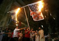 Lebanese Muslim demonstrators burn the US (R) and Israeli flags during a protest against a film mocking Islam in Abra, east of Sidon. As anti-American protests erupt in the Muslim world, the United States is powerless to act against those who incited the violence due to the freedoms enshrined in its cherished constitution