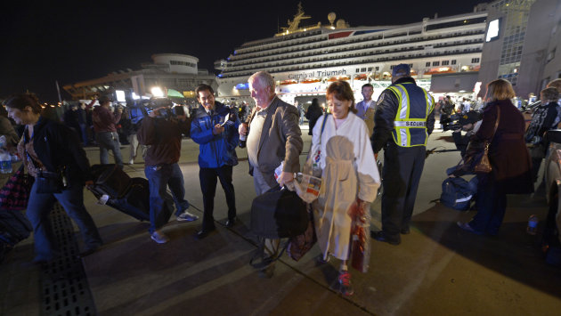 Passengers from the cruise ship Carnival Triumph are questioned by reporters after they disembarked in Mobile, Ala., Thursday, Feb. 14, 2013. The ship with more than 4,200 passengers and crew members