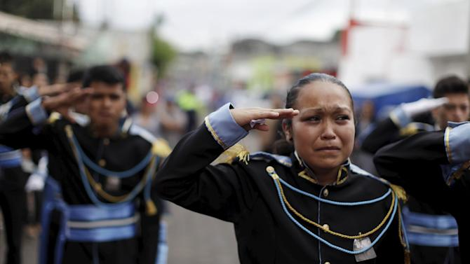 Bandmates salute as they participate in the funeral of Bryan Sandoval, a mudslide victim in Santa Catarina Pinula