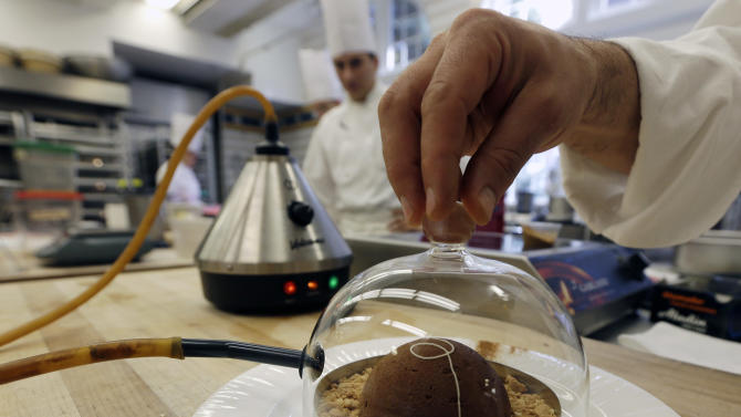 In this image taken on Friday, Sept. 14, 2012, cinnamon aroma is added to a peanut butter and milk chocolate dome dessert at the Culinary Institute of America in Hyde Park, N.Y. This esteemed cooking school north of New York City is dramatically pumping up science instruction, saying that tomorrow's chefs will need more technical know-how in the age of molecular gastronomy and sous-vide. (AP Photo/Mike Groll)