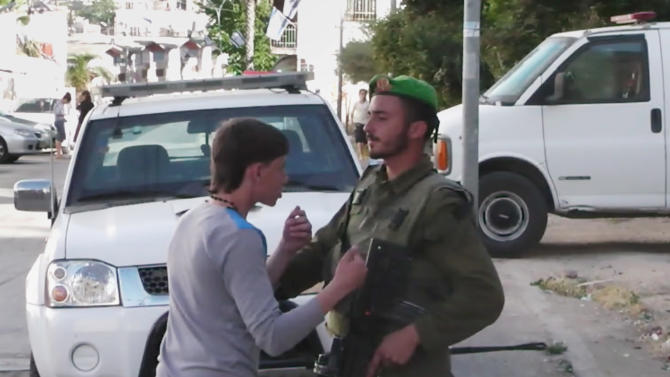 a group of Palestinian activista Palestinian teen confronts an Israeli soldier
