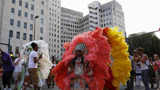 Members of the Creole Wild West Mardi Gras Indian Tribe parade past Charity Hospital, closed and vacant since Hurricane Katrina, in a second line parade to mark the tenth anniversary of the storm in New Orleans