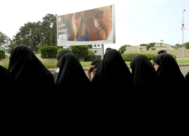 Lebanese Shiite Muslim women gather in front of a billboard bearing a huge portrait of Pope Benedict XVI at the entrance of Beirut international airport to welcome the pontiff who arrived on September