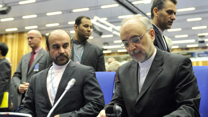 Iran's Ambassador to the International Atomic Energy Agency, IAEA, Reza Najafi and head of the Atomic Energy Organization of Iran, Ali Akbar Salehi, from left wait for the start of the IAEA general conference at the International Center in Vienna, Austria, Monday, Sept. 16, 2013. (AP Photo/Hans Punz)