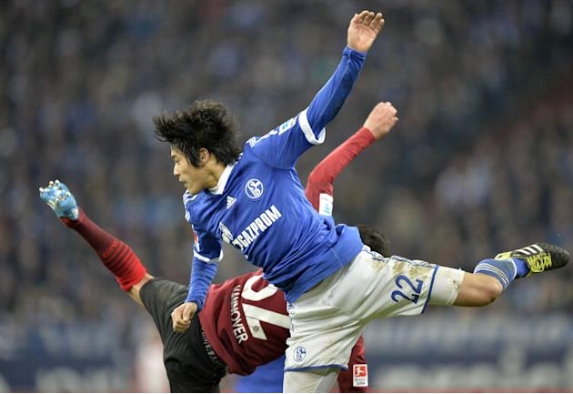 Schalke's Atsuto Uchida, in front, jumps with Hannover's Leonardo Bittencourt during the German Bundesliga soccer match between FC Schalke 04 and SV Hannover 96 in Gelsenkirchen,  Germany, Sun