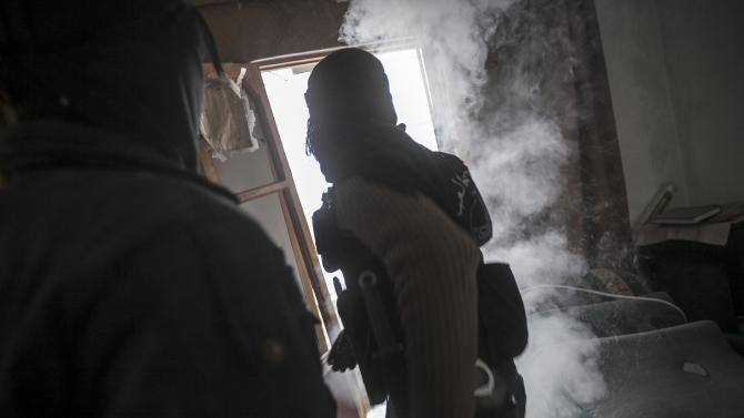 In this Friday, Dec. 07, 2012 photo, Syrian rebels throw a smoke device during clashes with troops loyal to President Bashar Assad in Aleppo, Syria. As fears grow in the West that Assad will unleash chemical weapons as an act of desperation, NATO moved forward Thursday with its plan to place Patriot missiles and troops along Syria's border with Turkey to protect against potential attacks. (AP Photo/Narciso Contreras)