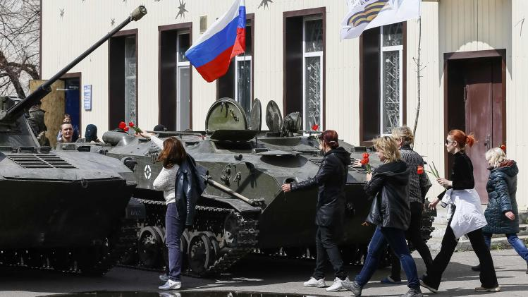 Local residents bring flowers to place them on armoured personnel carriers in Slaviansk