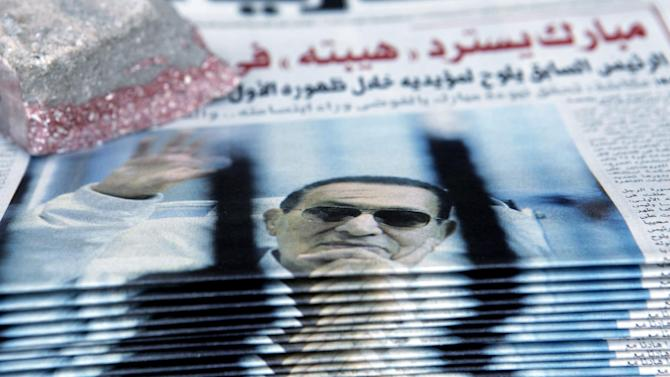"A stack of copies of an Egyptian newspapers with a picture of former Egyptian President Hosni Mubarak waving behind bars during a trial hearing Saturday appear on the newsstand in Tahrir Square, Cairo, Egypt, Sunday, April 14, 2013. The judge in Hosni Mubarak's retrial recused himself at the start of the first session on Saturday, citing a conflict of interest as the former Egyptian president appeared in court for the first time in 10 months grinning and waving to supporters. Arabic reads, ""The judge's recusal takes Mubarak's case to square one."" (AP Photo/ Amr Nabil"