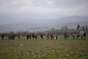Migrants walk through a field at the northern Greek …