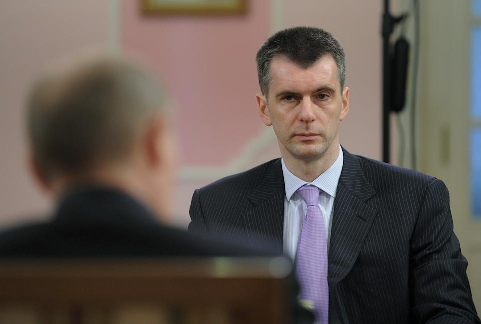 Presidential candidates billionaire Mikhail Prokhorov, background and Prime Minister Vladimir Putin meet in the village of Zhukovka near Moscow  on Monday, March 5, 2012. (AP Photo/RIA Novosti, Alexei Druzhinin, Government Press Service)