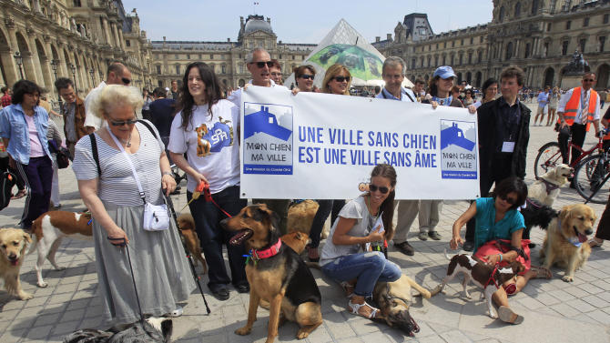 Dog owners pose near the Louvre, in Paris, Saturday June 8, 2013. At least 100 pooches with owners in tow, holding leashes marched near the Louvre at a demonstration to demand more park space and access to public transport for the four-legged friends. Sign reads: A City without Dogs is a City Without Soul. (AP Photo/Remy de la Mauviniere)