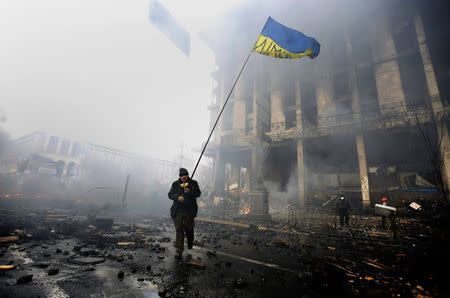 File photo of an anti-government protester holding a Ukranian flag as he advances through burning barricades in Kiev