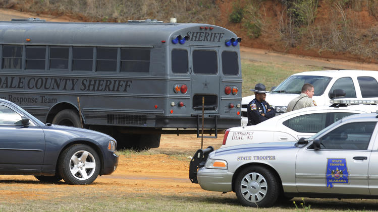 Police SWAT teams and hostage negotiators are gathered at standoff and hostage scene in Dale County near Midland City, Ala. on Wednesday Jan. 30, 2013. Authorities were locked in a standoff Wednesday with a gunman authorities say on Tuesday intercepted a school bus, killed the driver, snatched a 6-year-old boy and retreated into a bunker at his home in Alabama. (AP Photo/Montgomery Advertiser, Mickey Welsh)