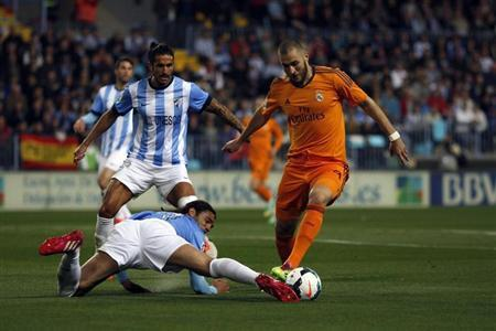 Real Madrid's Karim Benzema battles for the ball with Malaga's Sergio Sanchez during Spanish First Division soccer match in Malaga