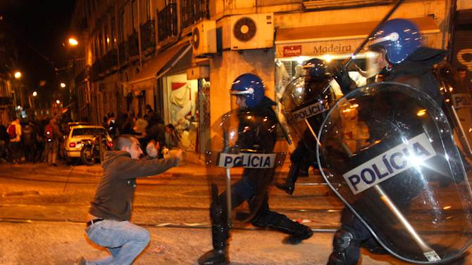 Riot police charge during clashes with protestors in Lisbon during a general strike Wednesday, Nov. 14 2012. The second general strike in eight months in Portugal, where the government intends to intensify austerity measures next year, left commuters stranded as trains ground to a virtual halt and the Lisbon subway shut down. (AP Photo/Francisco Seco)