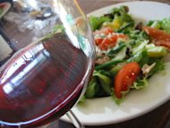 A glass of red wine is served with a salad.