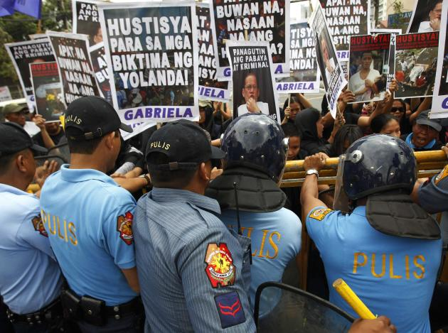Anti-riot policemen block the women's advocacy group GABRIELA and victims of Typhoon Haiyan during a International Women's Day protest rally outside the residence of President Benigno Aquino i
