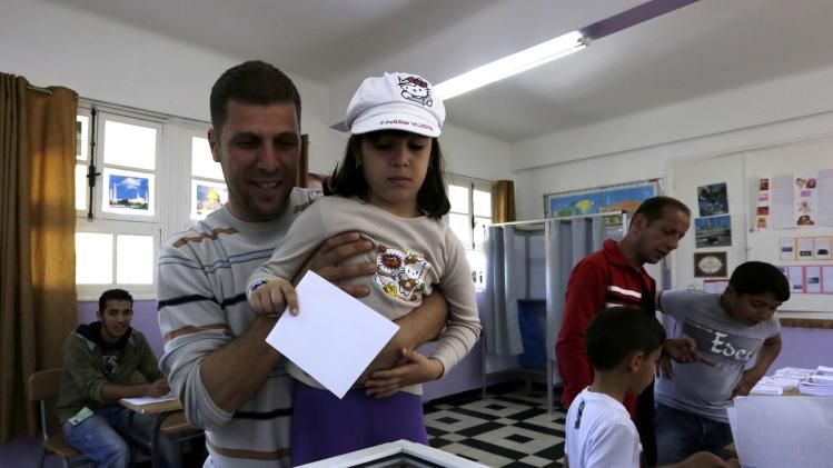 Man casts a ballot with his daughter during the presidential election in Algiers
