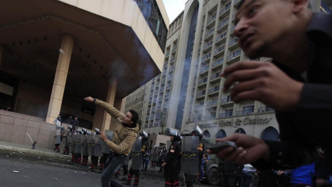 Pro and anti- government protesters clash in front of the Semiramis Intercontinental hotel, background left, near Tahrir Square, Cairo, Egypt, Tuesday, Jan. 29, 2013. Since Saturday, the Nile-side Semiramis Intercontinental has been on the front line of clashes between riot police and angry youths, with both sides throwing stones at each other along the city's famed Corniche promenade while tear gas wafted several stories up inside the building. (AP Photo/Khalil Hamra)