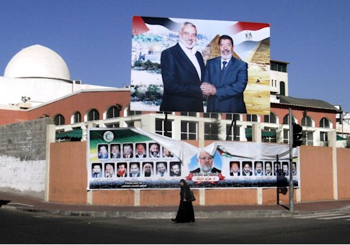 A Palestinian woman walks past a poster of Gaza's Hamas Prime Minister Ismail Haniyeh, left, and Egyptian President Mohammed Morsi in Gaza City, Saturday, Aug. 25, 2012. Hamas had hoped the Islamists who took charge in Egypt  this summer would swiftly turn their shared border crossing into a free-flowing trade route. However, a senior Hamas official acknowledged that Egyptian President Mohammed Morsi hasn't promised much and that it's time to scale back expectations of dramatic change. (AP Photo/Hatem Moussa)