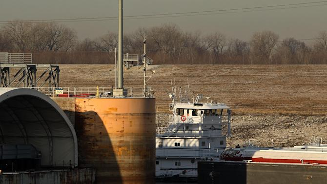 A towboat pushes a barge through Lock & Dam 27 early Wednesday, Jan. 23, 2013, in Granite City. Ill. A key stretch of the Mississippi River reopened to shipping Wednesday after hasty repairs were made to a lock damaged by a barge, marking the latest victory for stewards of the drought-plagued waterway they have maneuvered to keep open. (AP Photo/St. Louis Post-Dispatch, Erik M. Lunsford)