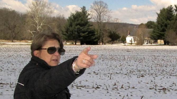 In this photo made on Tuesday, March 26, 2013, Carol Tanzola, president of Friends of Camp Security, points out the property on a 47-acre parcel, located about four miles east of York, Pa. It includes the spot where a 1979 archaeological study found numerous artifacts that confirmed local lore that the area had once served as Camp Security, a prison for the English, Scottish and Canadian soldiers who were captured after defeats in the battles of Saratoga and Yorktown. (AP Photo/Mark Scolforo)