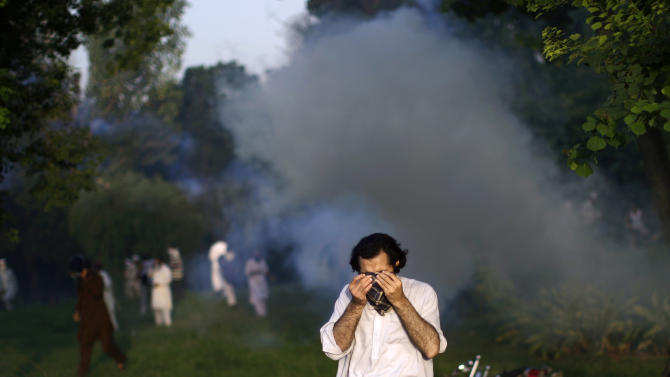 A Pakistani protester reacts to tear gas fired by police, during clashes erupted as protestors tried to approach the U.S. embassy, in Islamabad, Pakistan, Thursday, Sept. 20, 2012. Hundreds of Pakistanis angry at an anti-Islam film that denigrates the religion's prophet clashed with police in the Pakistani capital Thursday, the most violent show of anger in a day that saw smaller demonstrations in Indonesia, Iran and Afghanistan. The vast majority of Muslims have not taken to the streets over a film mocking the Prophet Muhammad, and behind the visible public anger a more measured debate is taking place over how much free speech is acceptable in the Muslim world. While many do yearn for more openness, few if any will go as far as accepting the right to blaspheme as the ultimate test of freedom of speech. (AP Photo/Muhammed Muheisen)