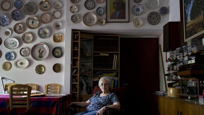 Cati Holland poses for a picture at her house in the Israeli city of Hadera, Thursday, July 25, 2013. Holland found out from an Israel-based social media genealogy company that is using the Internet to help match property stolen by the Nazis to heirs of the victims she was eligible for compensation for her grandmother's Berlin store seized by the Nazis more than 70 years ago. (AP Photo/Oded Balilty)
