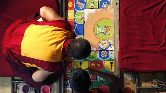 Buddhist monks work on fixing a sand mandala, which was disturbed by a small child at Jersey City City Hall, Friday, April 25, 2014, in Jersey City, N.J. The monks have been building the sand mandala since Monday. It's a traditional, multicolored display that is built then destroyed in a ceremony meant to symbolize the fleeting nature of life. The young child climbed over a rope barrier and got onto the four-foot-square display. The sides and middle were smudged as a result. (AP Photo/Julio Cortez)