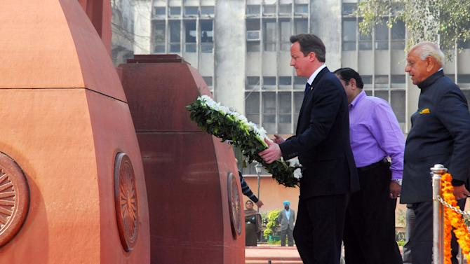 British Prime Minister David Cameron walks to lay a wreath at the site of a notorious 1919 massacre of hundreds of Indians by British colonial forces, in Amritsar, India, Wednesday, Feb. 20, 2013. Cameron's action Wednesday marked the first time a British premier made such a gesture of condolence at Jallianwala Bagh in the northwest city of Amritsar. More than 300 Indians were killed during the massacre on unarmed Indians attending a rally, which galvanized the national independence movement. (AP Photo)