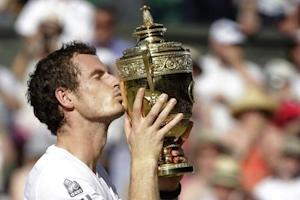 Andy Murray of Britain kisses the winners trophy after defeating Novak Djokovic of Serbia in their men's singles final tennis match at the Wimbledon Tennis Championships, in London