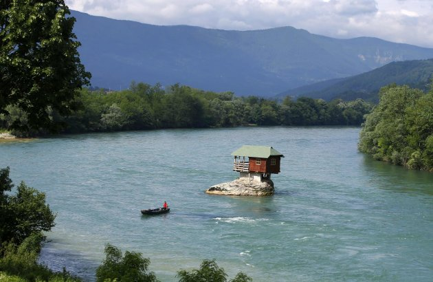 A man rows a boat near a tiny house build on a rock on the river Drina is seen near Bajina Basta