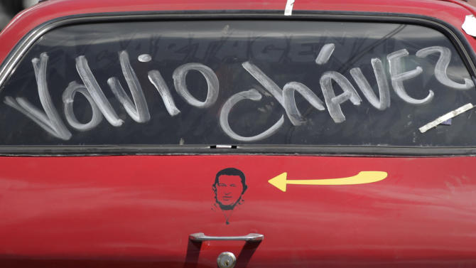 "The words in Spanish ""Chavez is back"" covers a red car's window above an image of Chavez on the car door in Caracas, Venezuela, Wednesday, Feb. 20, 2013.  President Hugo Chavez's sudden return to Venezuela after more than two months of cancer treatments in Cuba has fanned speculation that the president could be preparing to relinquish power and make way for a successor and a new election. (AP Photo/Ariana Cubillos)"