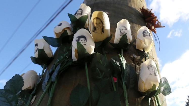 Roses with photos of shooting victims are posted on a light post at a makeshift memorial near the main intersection of the Sandy Hook village of Newtown, Conn., as the town continues to cope in the aftermath of the Sandy Hook Elementary School shooting, Wednesday, Dec. 19, 2012. The gunman, Adam Lanza, walked into Sandy Hook Elementary School in Newtown,  Dec. 14, and opened fire, killing 26 people, including 20 children, before killing himself. (AP Photo/Julio Cortez)