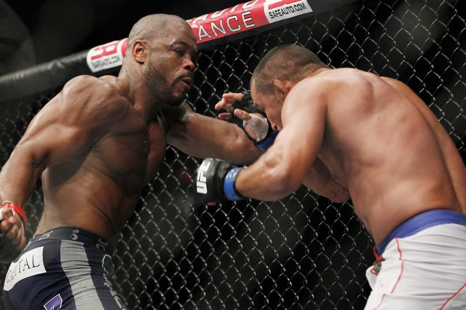 Rashad Evans backs Dan Henderson into a corner during UFC 161 in Winnipeg, Manitoba on Saturday June 15, 2013. (AP Photo/The Canadian Press, John Woods)