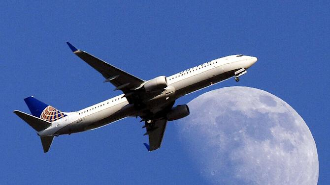 FILE - In this July 17, 2013 file photo, a United Airlines jet plane landing at Los Angeles International Airport, in Whittler City Calif., passes in front of a Waxing Gibbous moon. United Airlines reports quarterly earnings on Thursday, April 24, 2014. ( AP Photo/Nick Ut, File)