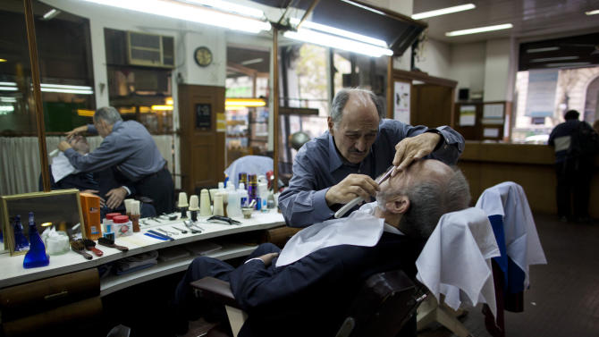 In this May 14, 2013 photo, barber Mario Saliche shaves a customer at the Romano hairdresser and barber shop in Buenos Aires, Argentina. With an Argentine on the throne of St. Peter, the South American country's capital city has launched a series of guided tours, that include the Romano's barber shop, where Bergoglio had a monthly haircut for 20 years. Three-hour weekend bus trips and walking tours are so far non-commercial in the first step at papal tourism. The bus tours wind through Buenos Aires twice each Saturday and Sunday and can carry about 40 passengers, cruising past 24 sites linked to the new pope. There's no charge for the trip, or for more limited walking tours of downtown and neighborhood sites Tuesdays and Thursdays. (AP Photo/Natacha Pisarenko)