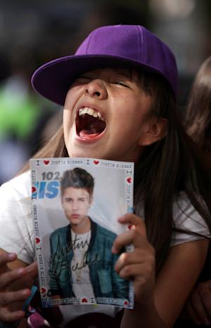 A fan of pop star Justin Bieber cheers outside a hotel where Bieber gave a news conference in Mexico City, Monday, June 11, 2012. Bieber will perform in a free open-air concert tonight at the Mexico City's main historic plaza, the Zocalo. (AP Photo/Alexandre Meneghini)