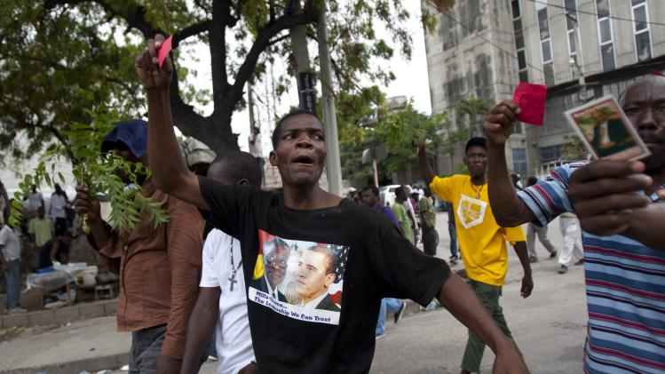 A demonstrator wears a T-shirt with an image of President Barack Obama, right, and Ghana's President John Atta Mills during a protest against Haiti's President Michel Martelly government in Port-au-Prince, Haiti, Sunday, Sept. 30, 2012. (AP Photo/Dieu Nalio Chery)